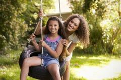 Madre che spinge figlia sull'oscillazione della gomma in giardino Fotografia Stock Libera da Diritti