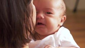 Madre che tiene e che lenisce gridando neonata archivi video