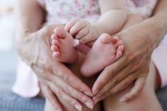 Madre che tiene i piedi del suo bambino, primo piano fotografia stock libera da diritti