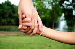 Madre che tiene il suo braccio del bambino Fotografia Stock