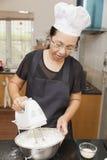 Madre che usando miscelatore elettrico per mescolare gli ingredienti del pan di Spagna Fotografie Stock