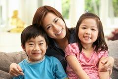 Madre china y niños que se sientan en el sofá foto de archivo libre de regalías