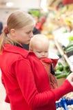 Madre con compras de la hija del bebé en supermercado Imagen de archivo libre de regalías