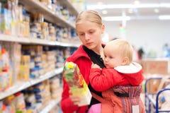 Madre con compras del bebé en supermercado Fotografía de archivo