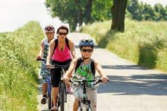 Madre con dos hijos en viaje de la bicicleta Imagenes de archivo