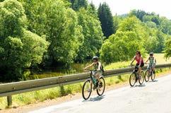 Madre con dos hijos en viaje de la bicicleta Imagen de archivo libre de regalías