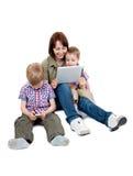 Madre con dos hijos y ordenadores de la tablilla Fotos de archivo
