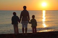 Madre con dos niños en la playa Imagen de archivo libre de regalías