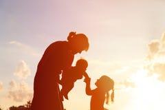 Madre con dos niños en la puesta del sol, familia feliz Imagen de archivo