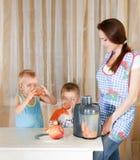 Madre con due bambini che fanno spremuta Fotografia Stock Libera da Diritti