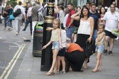 Madre con due figlie, vestite egualmente, supporto accanto alla strada, aspettante gli interruttori della luce di traffico immagine stock libera da diritti