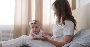 Madre con el bebé curioso en cama almacen de video