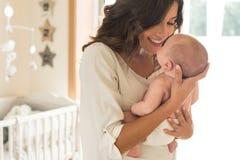Madre con el bebé en brazos imagenes de archivo