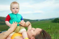 Madre con el bebé en hierba verde Imagen de archivo