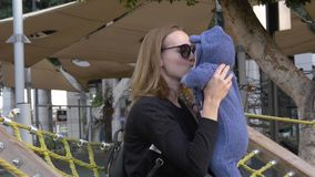 Madre con el bebé en manos que habla con el niño recién nacido en el patio almacen de metraje de vídeo
