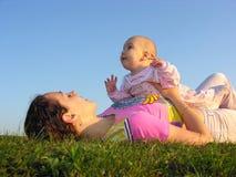Madre con el bebé en mentira de la puesta del sol Fotos de archivo libres de regalías
