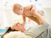 Madre con el bebé juguetón en casa fotografía de archivo libre de regalías