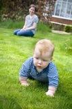 Madre con el bebé que aprende arrastrarse Foto de archivo libre de regalías