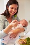 Madre con el bebé que come la comida sana en cocina Fotografía de archivo libre de regalías