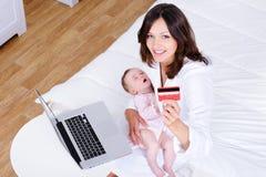 Madre con el bebé que hace compras del Internet Imagen de archivo