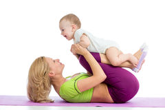 Madre con el bebé que hace la gimnasia en la estera de la aptitud Imagen de archivo libre de regalías