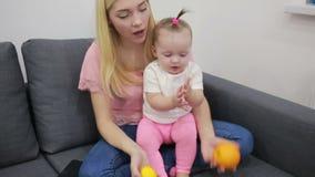 Madre con el bebé que juega en el sofá almacen de metraje de vídeo