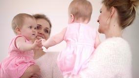 Madre con el bebé que mira el espejo Niño dulce que juega con el espejo almacen de metraje de vídeo