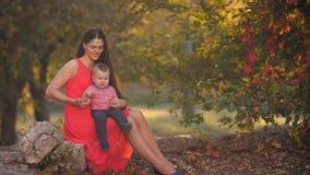 Madre con el bebé que presenta en la naturaleza almacen de metraje de vídeo