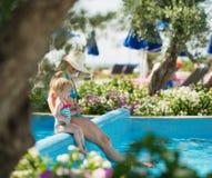 Madre con el bebé que se sienta en cara de la piscina Fotografía de archivo libre de regalías