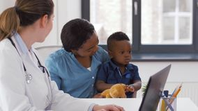 Madre con el bebé y el doctor con el ordenador portátil en la clínica almacen de metraje de vídeo