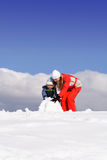 Madre con el cabrito que hace el muñeco de nieve Fotografía de archivo