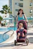 Madre con el cochecito de niño que recorre en el centro turístico Imágenes de archivo libres de regalías