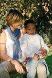 Madre con el color del niño adoptado Fotos de archivo