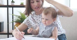Madre con el dibujo de la hija del bebé en el papel almacen de metraje de vídeo