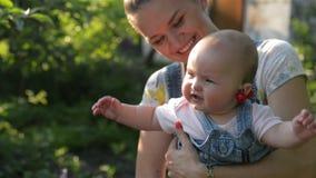 Madre con el gir del bebé en jardín, mamá sonriente joven que detiene a su hija y que juega en el al aire libre almacen de metraje de vídeo