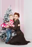 Madre con el hijo cerca del árbol de abeto con el regalo La Navidad, Año Nuevo Imágenes de archivo libres de regalías