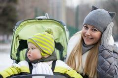 Madre con el hijo de dos años en parque del invierno Imágenes de archivo libres de regalías