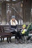 Madre con el hijo de dos años en parque del invierno Foto de archivo