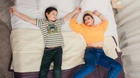 Madre con el hijo en cama, madre e hijo que se divierten Foto de archivo libre de regalías