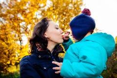 Madre con el hijo en jardín del melocotón del otoño Imagen de archivo