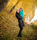 Madre con el hijo en jardín del melocotón del otoño Fotografía de archivo