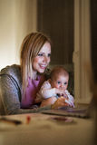 Madre con el hijo en los brazos, trabajando en el ordenador portátil Imagen de archivo