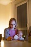 Madre con el hijo en los brazos, trabajando en el ordenador portátil Fotos de archivo