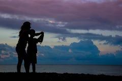 Madre con el hijo hacer las fotos del mar en la puesta del sol con las nubes rosadas fotos de archivo