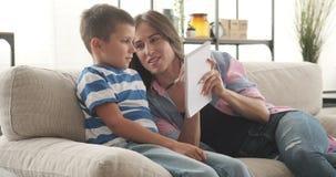 Madre con el hijo que elabora la lista de compras en libreta almacen de metraje de vídeo