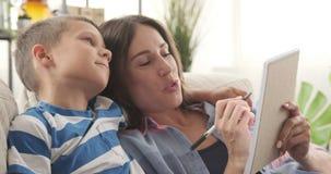 Madre con el hijo que elabora la lista de compras en libreta metrajes