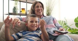 Madre con el hijo que se divierte que ve la TV en casa almacen de metraje de vídeo