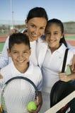 Madre con el hijo y la hija por la red en el retrato del campo de tenis Foto de archivo libre de regalías