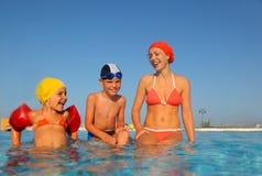 Madre con el hijo y la hija que se sientan en piscina Imagen de archivo libre de regalías