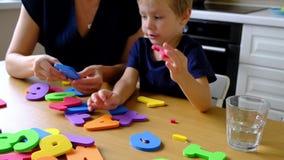 Madre con el muchacho preescolar que aprende alfabeto inglés y números almacen de metraje de vídeo